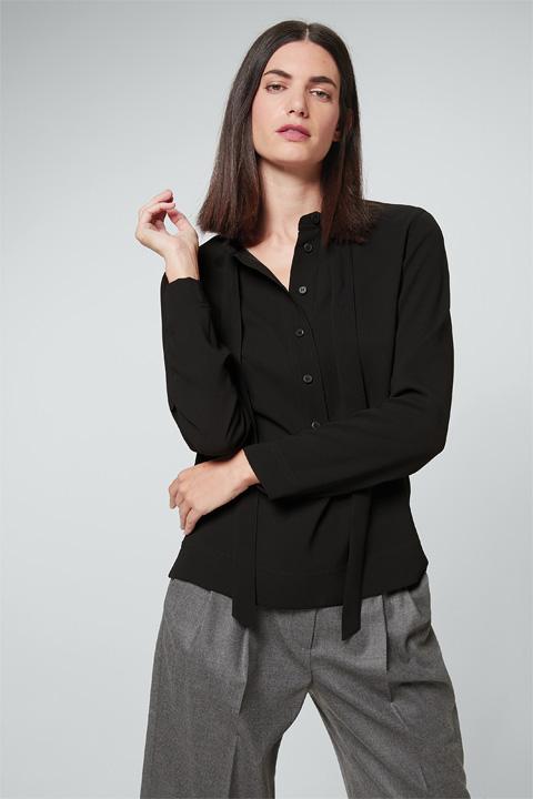 Artikel klicken und genauer betrachten! - Die elegante Crêpe-Bluse aus dem Hause windsor. präsentiert sich in raffinierter Optik mit kurzer Knopfleiste und einem Stehkragen mit Schluppe als stilvolles Bindedetail. Die lockere Passform in fließender A-Linie verleiht Outfit-Kombinationen mit Röcken, Hosen und Business-Kostümen ein luxuriöses Finish. Klassisch-edel wirkt das Essential in der schwarzen Nuance zu den passenden Crêpe-Hosen. | im Online Shop kaufen